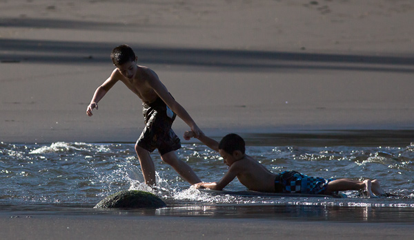 Kids playing on the Waipi'o Valley beach, Big Island, Hawaii. © Carl Amoth