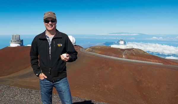 Carl on Mauna Kea's 13,803 ft summit with snowball in hand. This is one of the best sites in the world for astronomical observation, hence the numerous observatories.
